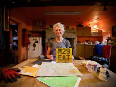 Nicky at home on her farm in Yorkshire, UK, before flying out to the race in the USA. Nicky holds a vehicle registration plate. Each participant must take a vehicle registration plate to the race and give it to the organiser as part of their entry fee.